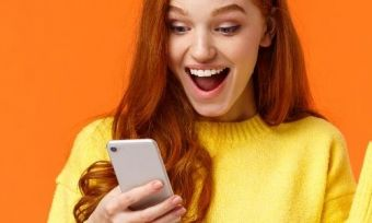 A person looking at a phone excitedly