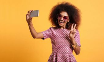 Young woman in red dress taking selfie with peace sign