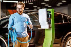 Man at electric vehicle charging station