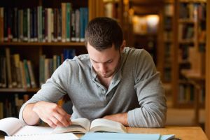Male student studying in library