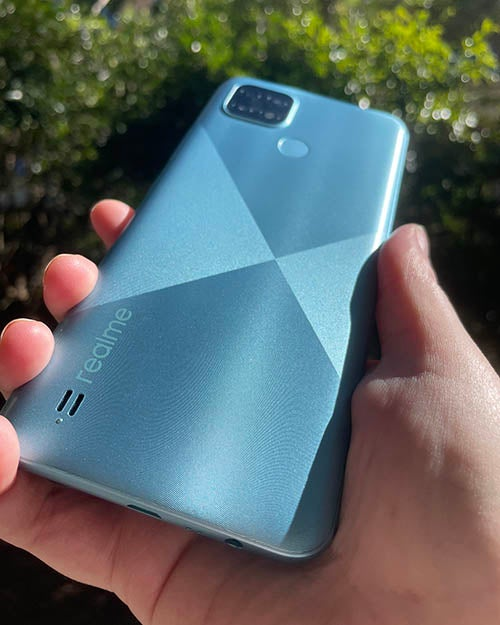 Back of Realme C21 phone in blue being held