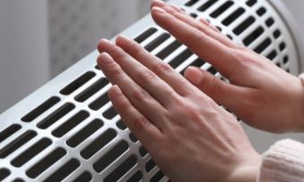 Hands over heater inside living room