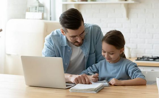 Father helping daughter with homework at laptop