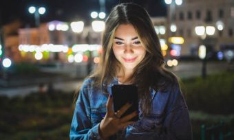 Woman using smartphone outdoors at night
