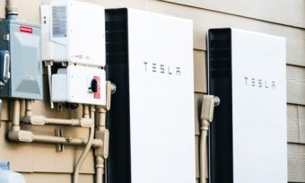 Tesla solar battery in home next to energy meter