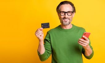 Man holding phone and credit card against yellow background