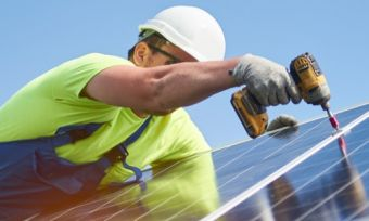 Tradesman installing solar panels on roof of home