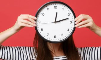 Woman holding clock over face signifying long wait times with red background