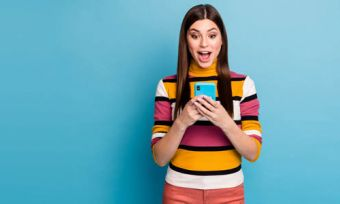 Young woman looking at phone with excited expression standing against blue background