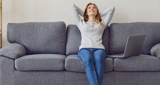 Lady sitting on lounge comfortable next to laptop