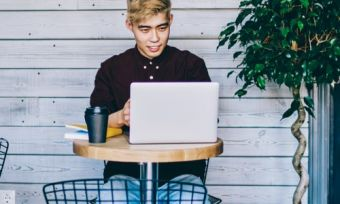 Man with laptop at cafe browsing internet