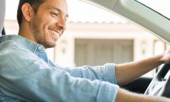 Man cheerfully driving a car