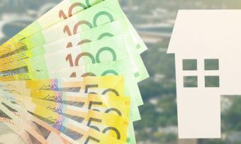Australian dollars next to cardboard cut out of a house.