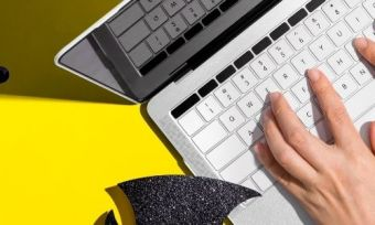 A person using a laptop surounded by halloween decorations