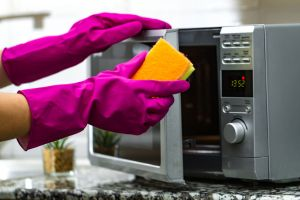 Cleaning microwave with glove