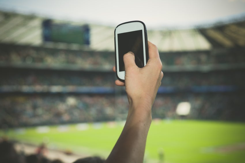 Hand filming sports event on phone